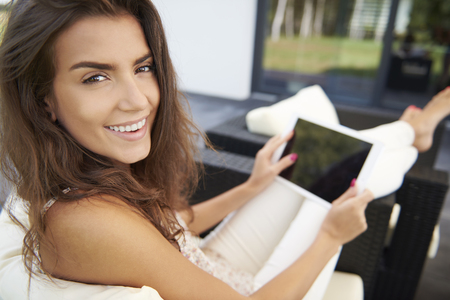women sitting: Its a mercy that I have wireless Internet here Stock Photo