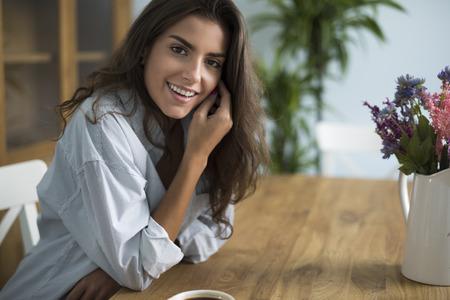 belle brune: Jeune femme café potable dans la salle à manger Banque d'images