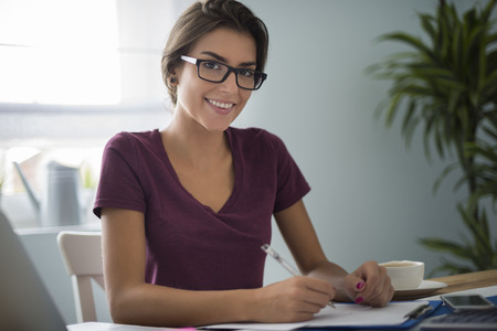 toothy smiles: Dutiful woman at her house office Stock Photo
