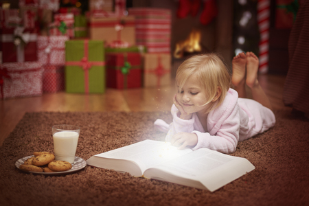 cute christmas: Little girl reading book about amazing adventures