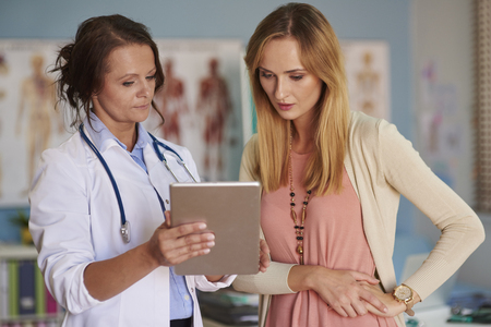 medical exam: Doctor showing examination results on the digital tablet Stock Photo