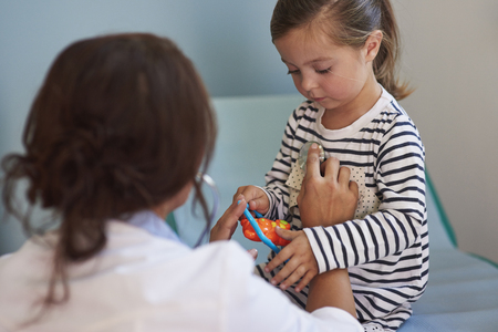 dutiful: Doctor examining her very little patient