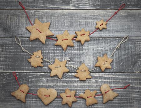 decoracion mesas: Panes de jengibre en forma de la Navidad en la cuerda Foto de archivo