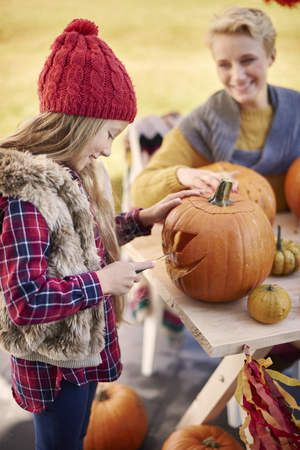 carvings: Affectionate girl carving a pumpkin in the garden Stock Photo