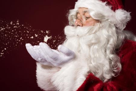 Kerstman blaast wat sneeuwvlokken