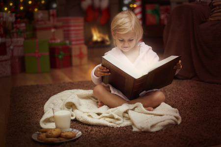 charming girl: Charming girl reading some Christmas tales Stock Photo