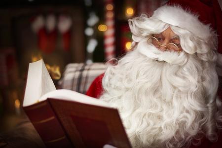 santa clos: Pap� Noel que lee la biblia santa en el interior de una casa Foto de archivo