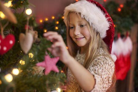 albero della vita: Bambina appesa alcuni ornamenti di Natale Archivio Fotografico