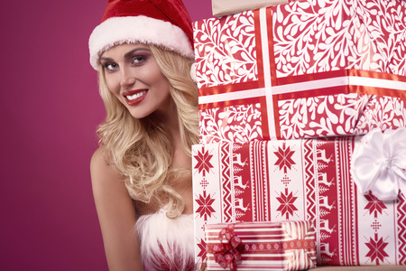 flirty: Flirty santa claus with a pile of gifts Stock Photo