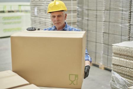 倉庫で中年の男性が努力