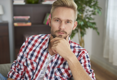 Young pensive man in his living room Stock Photo