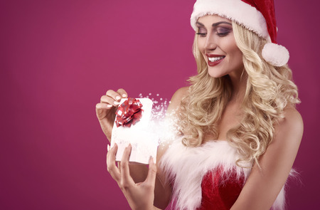 mujer pensativa: Sexy santa is opening magic christmas box