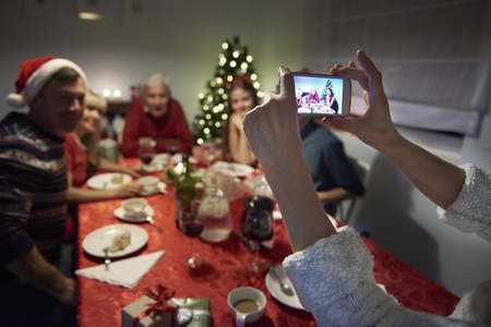 holiday lights display: Unrecognizable person taking photography of the family