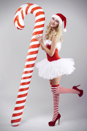 woman posing: Feminine santa claus leaning on a candy cane Stock Photo