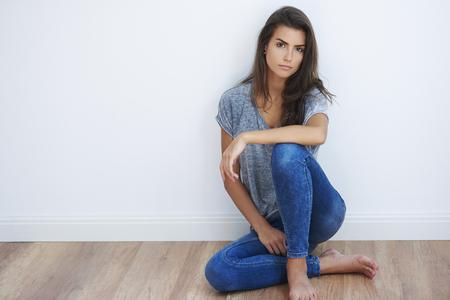 Donna che si siede sul pavimento di legno Archivio Fotografico - 48559757