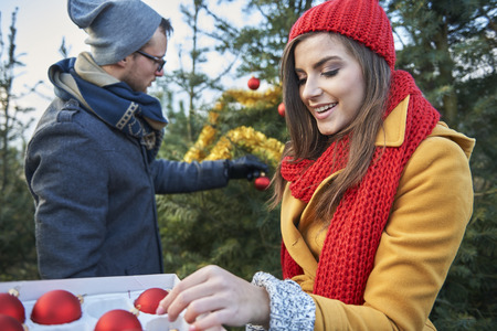 winter woman: Christmas tree in the garden also must be dressed Stock Photo