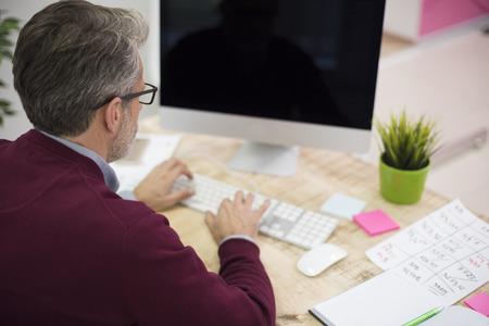 high angle: High angle view of a man working on the computer