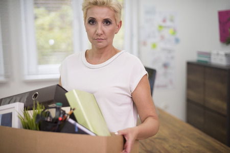 dismissal: Fired woman carrying a box with some content Stock Photo