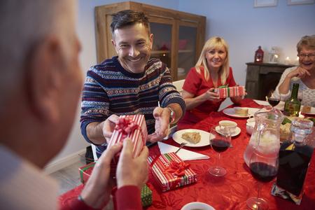 comida de navidad: Hombre sonriente que da un presente a su padre Foto de archivo