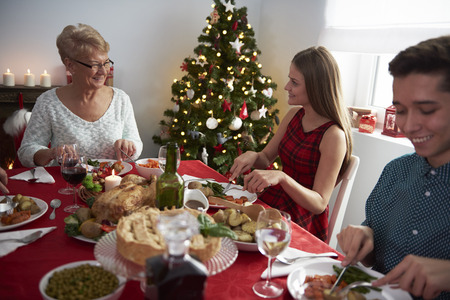eating dinner: Grandmother and her grandchildren at Christmas table Stock Photo
