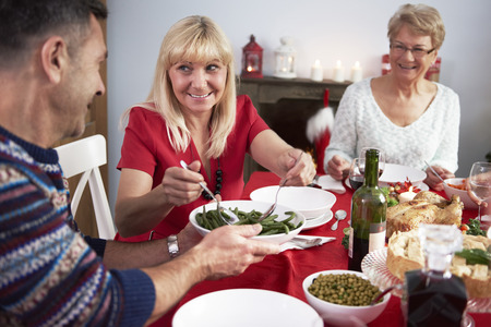 woman eat: Wife helps her husband at Christmas Eve