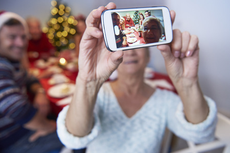 holiday lights display: Modern grandmother taking a photo of the family