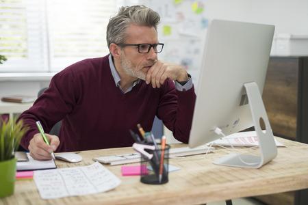 Zamyšlený člověk tvrdě pracuje na počítači