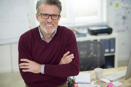 busy beard: Portrait of cheerful man sitting on the desk Stock Photo