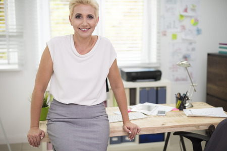 office manager: Cheerful woman leaning on the desk
