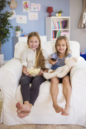 toothy smile: Elementary age girls waiting for their favorite TV programme