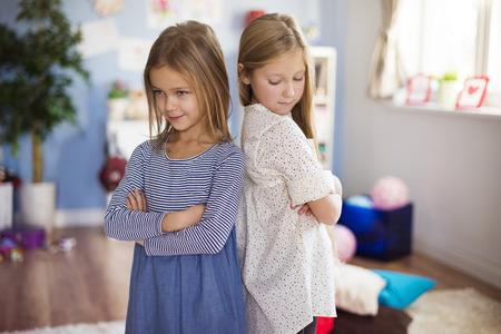 turn away: Sulking girls stading back to back