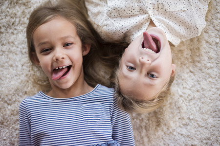 facial expression: Funny facial expression of two cute girls Stock Photo
