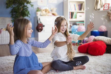 Cross legged sitting girls and soap bubbles