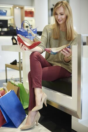 legs crossed at knee: Great variety in the shoe shop Stock Photo