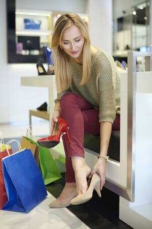 legs crossed at knee: Woman trying on a new pair of shoes