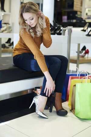 shoes woman: Woman cant decide which shoes to buy Stock Photo