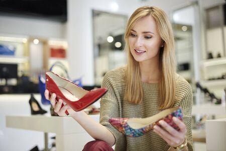 comprando zapatos: Mujer atractiva que hace difícil decisión Foto de archivo