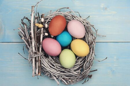 fulfilled: Bird nest fulfilled with pastel color eggs Stock Photo