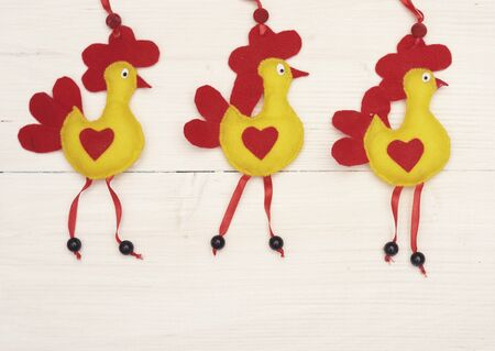 red hen: Felt easter chickens on white plank
