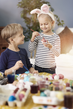 multi age: Proud of sister how paint Easter egg Stock Photo