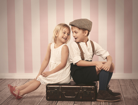 two children: Two children sitting on the wooden suitcase