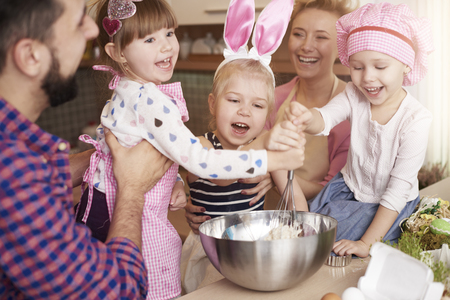 children learning: Parents and their children baking together Stock Photo