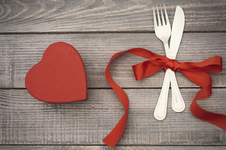 love shape: Silverware and chocolate box on the wooden plank
