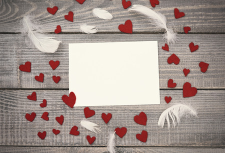 surrounding: Empty paper in the surrounding of textile hearts and feathers Stock Photo