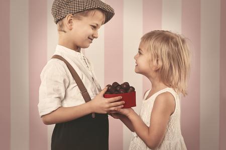 receiving: Boy giving a girl box full of chocolates Stock Photo