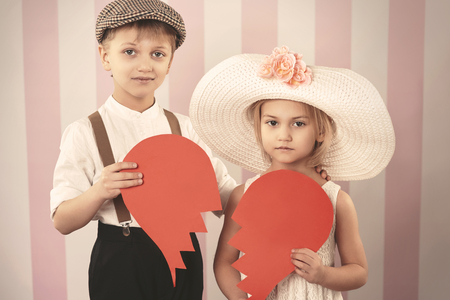 hearted: Broken hearted kid couple with a paper heart