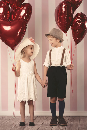 cute girl: Big bunch of balloons held by cute children Stock Photo