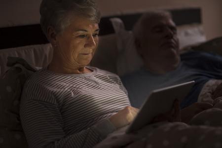 enamorados en la cama: Abuela navegar por Internet a altas horas de la noche Foto de archivo