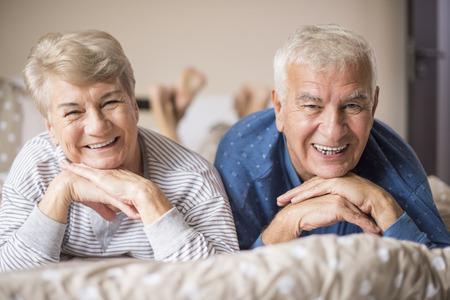elderly woman: Senior couple in pajamas on the bed