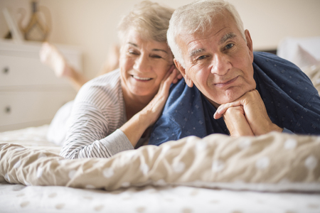 bed sheets: Happy senior couple lying down on the bed Stock Photo